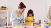 jardim de infância : mother and daughter cooking cupcakes at home