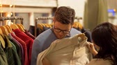 desgaste : couple choosing clothes at vintage clothing store Stock Footage