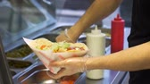 coisa : chef adding vegetables to pita at kebab shop