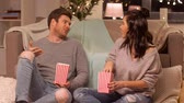 hyggelig : happy couple eating pop corn at home