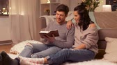 hyggelig : happy couple reading book at home