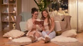 hyggelig : happy female friends reading book at home