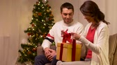 happy couple with christmas gift at home Vidéos Libres De Droits