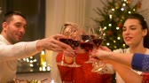 saúde : happy friends drinking red wine at christmas