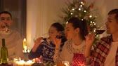 happy friends drinking red wine at christmas