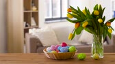 tulip : colored easter eggs in basket and flowers at home