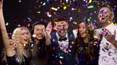 laço : happy friends at party under confetti over black