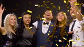 confete : happy friends at party under confetti over black