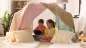 irmã : little girls with tablet pc in kids tent at home