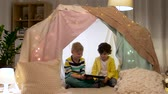 hyggelig : little boys with tablet pc in kids tent at home Stock Footage