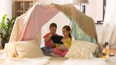 jardim de infância : little girls with tablet pc in kids tent at home