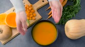 parcela : hands putting bowl of pumpkin cream soup on table