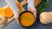 placa de corte : hands putting bowl of pumpkin cream soup on table