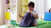apple : boy packing schoolbag with school supplies at home