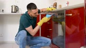 maintenance : man with rag cleaning oven door at home kitchen
