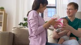 multirracial : happy family with gift and baby boy at home Stock Footage