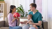 parentalidade : happy family with flowers and baby boy at home