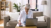 economia : senior woman with laptop and calculator at home Stock Footage