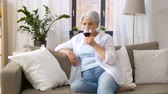 mais velho : senior woman drinking red wine from glass at home