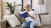 mais velho : senior woman reading book at home