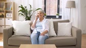 mais velho : senior woman calling on smartphone at home