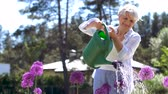 банки : senior woman watering flowers at summer garden