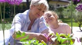 zahradník : grandmother and girl study flowers at garden