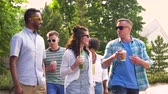 south american : friends drinking coffee and juice walking in park Stock Footage