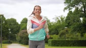 fino : woman with fitness tracker running in park Vídeos