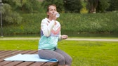 desportivo : woman drinking water after exercising in park Stock Footage
