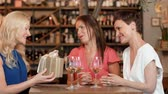 clinking : women giving present to friend at wine bar