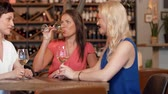 classic : happy women drinking wine at bar or restaurant