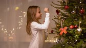 cana : happy girl decorating christmas tree at home