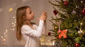 seasonal : happy girl decorating christmas tree at home