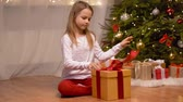 curiosidade : happy girl opening christmas gift at home