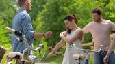 free country : happy friends with bicycles dancing at summer park