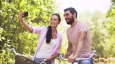 fixní : couple with bicycles taking selfie by smartphone