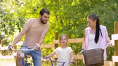 pre teen : happy family riding bicycles in summer park