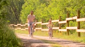 pre teen : father and daughter riding bicycles in summer park Stock Footage
