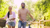 fixní : couple with bicycles walking along summer park