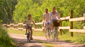 passeio : happy family riding bicycles in summer park