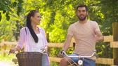fixní : happy couple with bicycles talking at summer park
