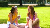 tatuagem : teenage girls with milk shakes at picnic in park