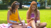 milk shake : teenage girls with smartphones and shakes in park