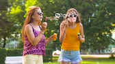 bolhas : teenage girls blowing bubbles in summer park