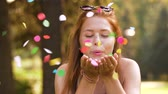 gondatlan : teenage girl blowing confetti off hands in park Stock mozgókép