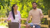 cyklus : happy couple with bicycles talking at summer park