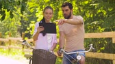 fixní : couple with tablet pc and bicycles at summer park