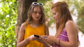 teenage girl : teenage girls with smartphones in summer park