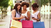 афроамериканца : women with smartphones and shopping bags in city